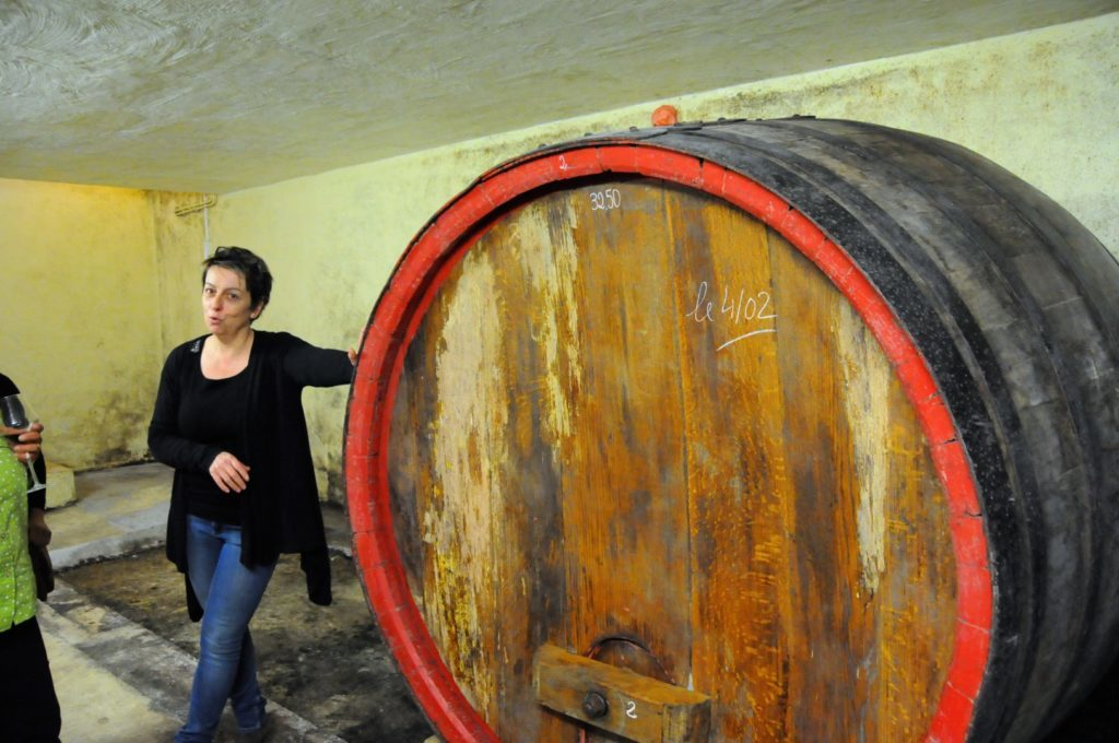 Véronique Cunty of Domaine de Font-Sane standing next to a large wine barrel.