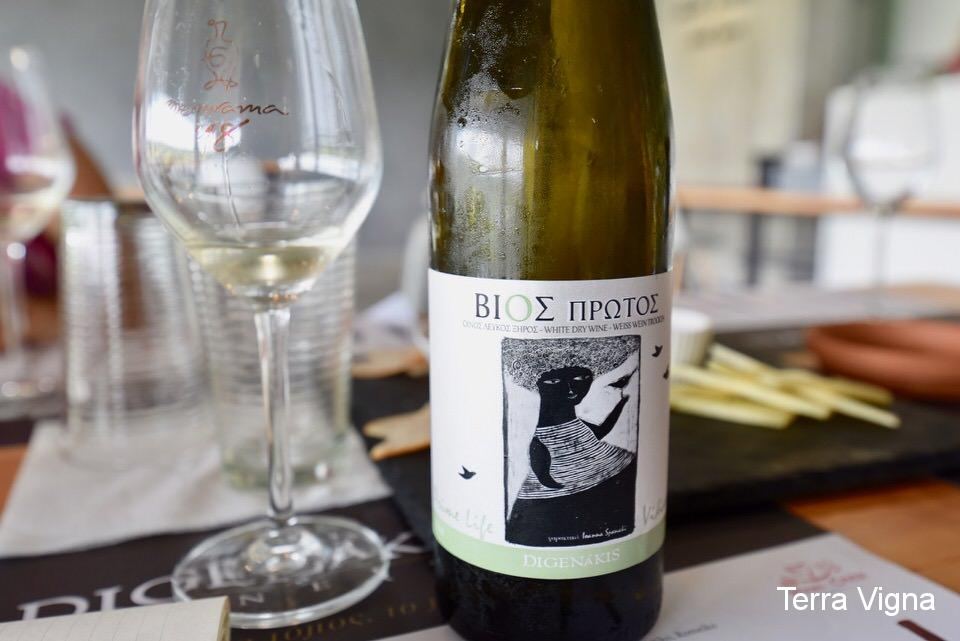 A bottle of Greek white wine next to a glass of white wine.